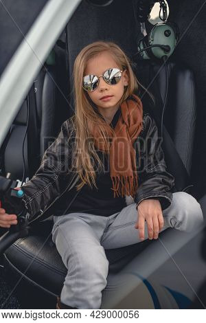 Laid-back Tween Girl Sitting On Pilot Seat In Helicopter