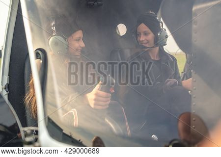 Two Happy Teen Girls In Pilot Headsets Talking In Helicopter Cockpit