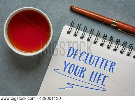 de-clutter your life - inspirational handwriting in a spiral notebook  with a cup of tea and  a pen, lifestyle and personal development concept