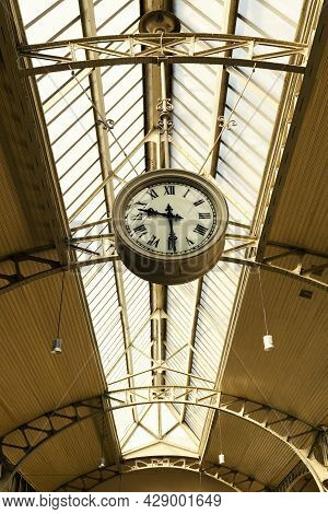 Vintage Clock With Roman Numerals Under The Glass Arched Ceiling Of The Railway Station (st. Petersb