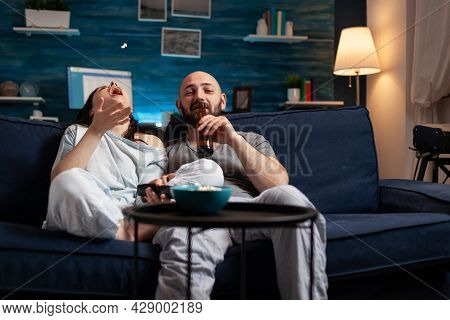 Relaxed Couple In Pajamas Relaxing On Sofa Eating Popcorn Watching Comedy Movie, Enjoying Free Time