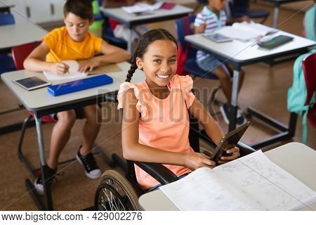Portrait of disabled african american girl smiling while sitting on wheelchair at elementary school. school and education concept