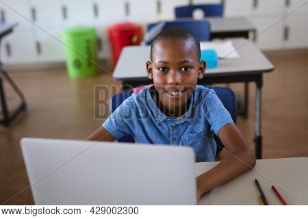 Portrait of african american boy smiling while using laptop sitting on his desk at elementary school. school and education concept