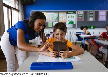 African american female teacher teaching a boy to use digital tablet in class at elementary school. education back to school health safety during covid19 coronavirus pandemic
