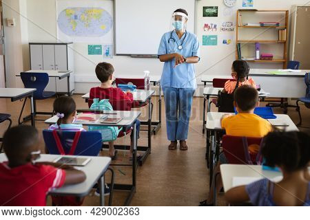 Female health worker wearing face shield talking to students in the class at elementary school. education back to school health safety during covid19 coronavirus pandemic.