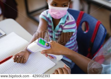 Mid section of female health worker measuring temperature of a girl at elementary school. education back to school health safety during covid19 coronavirus pandemic.