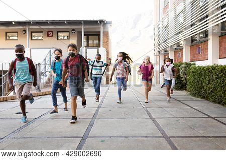 Group of diverse students wearing face masks running at elementary school. education back to school health safety during covid19 coronavirus pandemic.