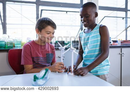 Caucasian boy and african american boy holding windmill models in science class at elementary school. school and education concept