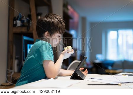 Healthy Boy Eating Red Apple For His Snack After Finished Homework,new Normal Life Kid Using Tablet