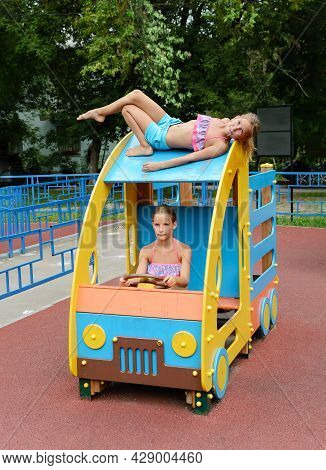 Tween Caucasian Girls Sits On Toy Wooden Car On Playground