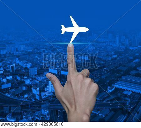 Hand Pressing Airplane Flat Icon Over Modern City Tower, Street, Expressway And Skyscraper, Business