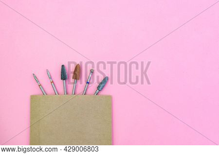 Replaceable Attachments For The Manicure Machine In A Craft Bag After Sterilization. On A Pink Backg