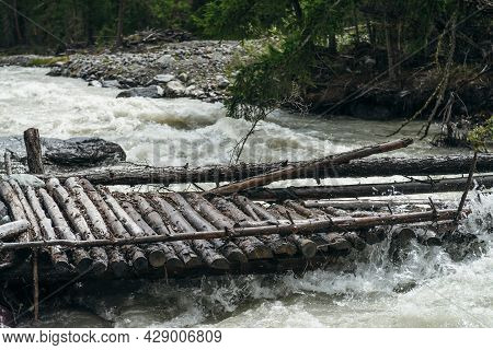 Fast Turbulent River With Broken Bridge In Water. Scenic Mountain Landscape With Log Bridge Across R