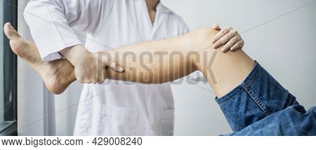 A Professional Physiotherapist Is Stretching The Patient's Legs, The Patient Has Muscle Dysfunction