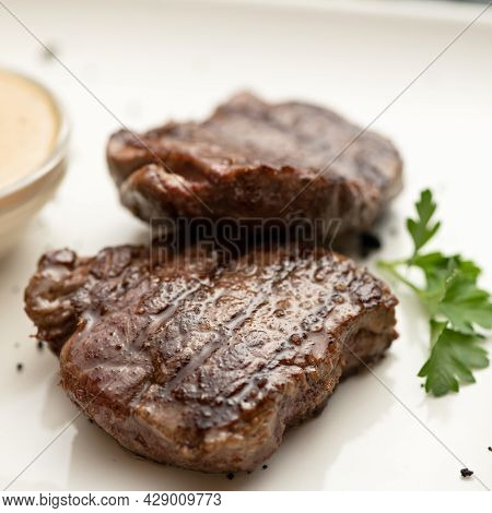 Grilled Tenderloin, Juicy Steak Or Meat Fillet With Herbs And Mustard On White Plate. Close-up Shot.