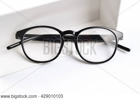 Optical Glasses In A Stylish Black Frame Are Located Near A White Gift Box On A White Background.the