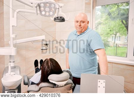 Dentist In Sterile Gloves Smiling To Camera While Standing Beside Female Patient. Woman Receiving St