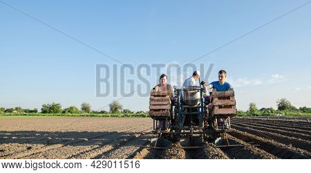 Workers On A Tractor Are Planting Potatoes. Automation Of The Process Of Planting Potato Seeds. Agri