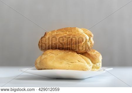 Homemade Delicate Profiteroles Or Eclairs Without Cream On Saucer. Gray Background