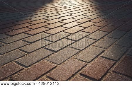 Summer Rays Of The Sun Gently Lie On The Road Of Paving Stones. The Light Of The Sun Illuminates The