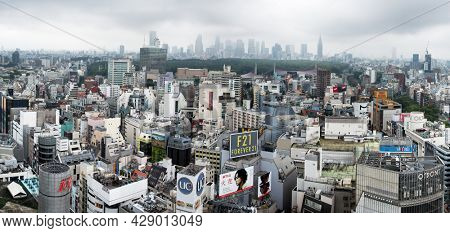 Tokyo, Japan - 23 June 2016: The modern skyscrapers of the financial district of Tokyo, seen from the Shinjuku district. Parkland separates the distinctly different areas of the city. Wide panorama