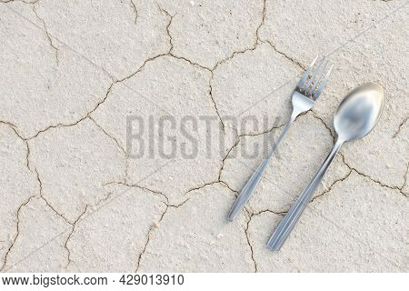 Cutlery On Cracked Dry Ground. Depletion Of Soil Resources. Fork And Spoon On Desert Sandy Soil. Ari