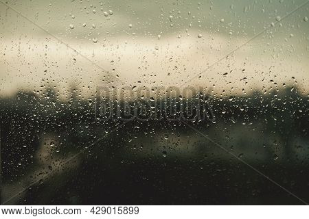 Rain Drops On Window Glasses Surface. Natural Pattern Of Raindrops On Cloudy Background.