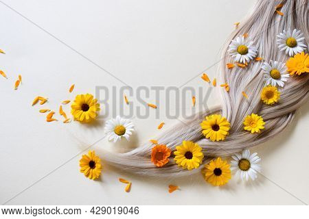 Pigtail. Chamomile And Calendula Flowers In Blond Hair.