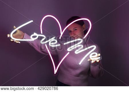 Beautiful Girl With Neon Signs. White And Pink Neon Heart With The Inscription Love Me. Trendy Style