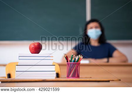 Back to School Concept. Apple, accessories and books in the classroom, teacher wearing mask in the background.