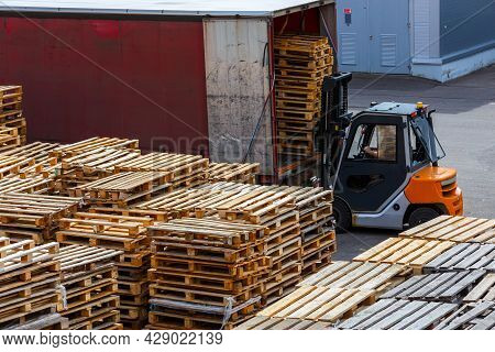 Forklift Loading Used Wooden Pallet Stacks Into Truck - Perspective View From Above