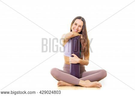 Young Sporty Female Yoga Instructor In Bright White Yoga Studio, Holding Yoga Mat, Smiling, Looking