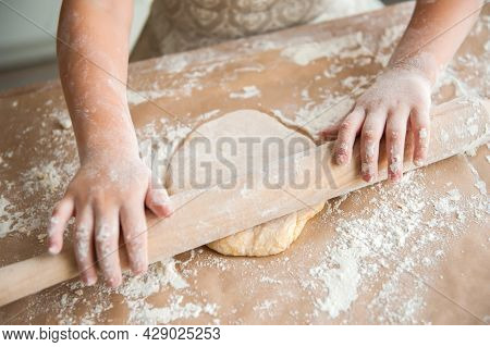 Little Girl Prepares Dough In The Kitchen. Rolls Out The Dough With A Rolling Pin. Close-up, Top Vie