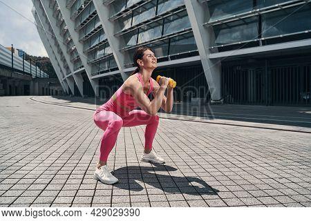Joyful Sportive Woman Squatting With Hand Weights