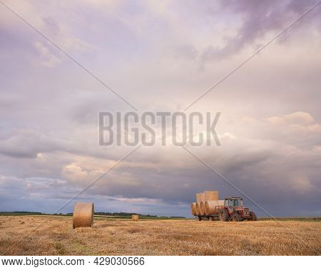 Landscape With Straw Bales And Tractor In French Ardennes Under Cloudy Sky During Sunset In Summer
