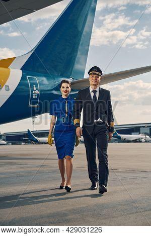 Aviator And A Flight Attendant Going Along The Runway