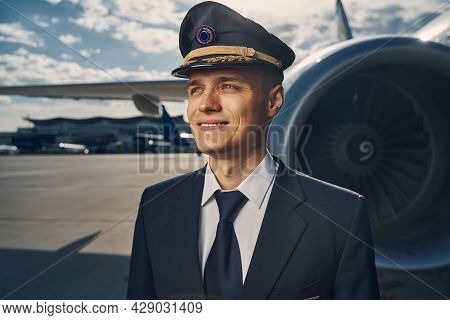 Smiling Airline Pilot In A Cap Gazing Into The Distance