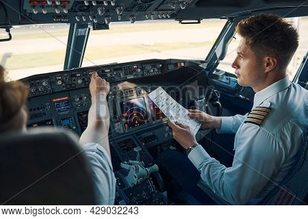 Airline Captain And First Officer Sitting In The Cockpit
