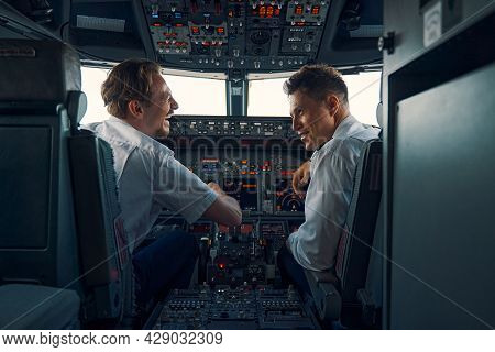 Two Aviators Sitting In The Cockpit Of An Aircraft