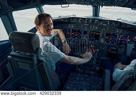 Joyful Chief Pilot Posing For The Camera In The Cockpit