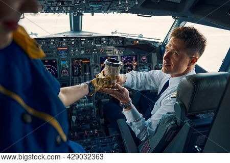 Stewardess Serving Coffee To A Pleased Co-pilot In The Cockpit