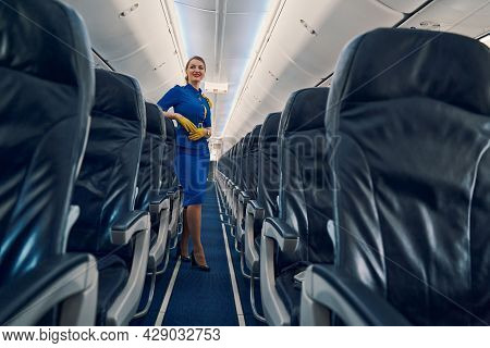 Happy Attractive Flight Attendant Standing In The Cabin Aisle