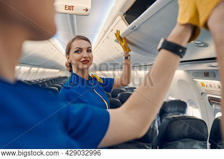 Flight Attendants Closing The Overhead Lockers In The Passenger Cabin