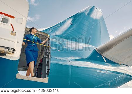 Smiling Pleased Flight Attendant Looking Out Of A Parked Aircraft