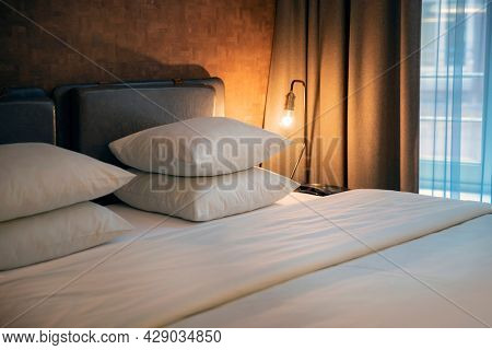 Nice Cozy Typical Hotel Room with Mild Warm Light. Double Bed with Clean White Linens. Contemporary Modern Room Decor. Perfect Lodging for Travel.