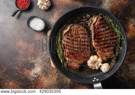 Grilled Picanha Organic  Beef Steaks On Pan With Herbs And Garlic. Over Old Dark Metall Background,