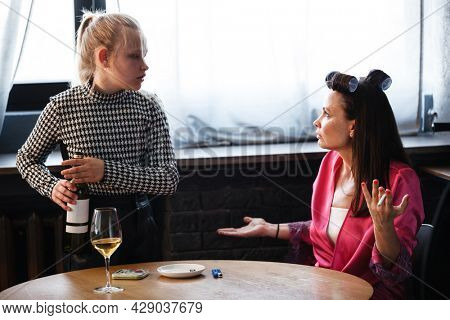 Alcoholism in family problem. Daughter aguring with her mother about drinking wine. Two people, woman and teenage girl quarrel in the kitchen. A depressed female is addicted to alcohol at home.