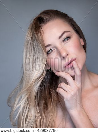 Closeup Portrait of a Beautiful Blond Woman Isolated on Gray Background. Fashion Girl with Natural Makeup and with Perfect Young Complexion.