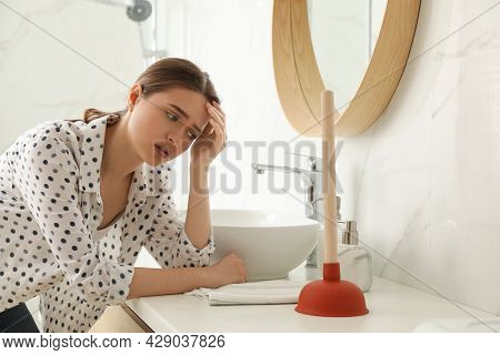 Unhappy Young Woman With Plunger Near Clogged Sink In Bathroom