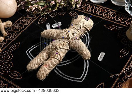 Voodoo Doll Pierced With Pins Surrounded By Ceremonial Items On Table. Curse Ceremony